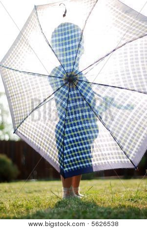 Little Boy Holding Umbrella Against The Sun
