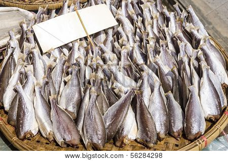 Rows of dry fish on pannier for sale in market.