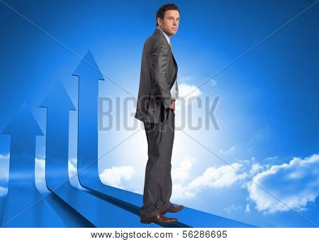 Serious businessman with hand on hip against arrows in the sky in blue