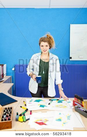 Industrial designer standing behind her desk, covered with sketches and product drawings, holding a coffee cup and smiling