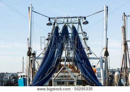 Blue Fishing Nets Or Trawl Hanging From Ship