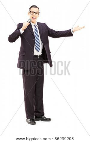 Full length portrait of a male announcer holding microphone, isolated on white background