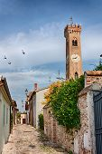 image of porphyry  - narrow alley in the ancient italian town Santarcangelo di Romagna with the antique clock tower on background - JPG