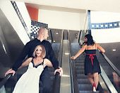 picture of escalator  - a couple riding down an escalator with the man looking at another woman - JPG