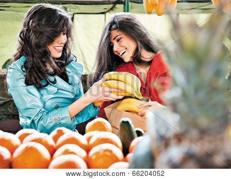 sisters shopping fruits at an outdoors farmers market