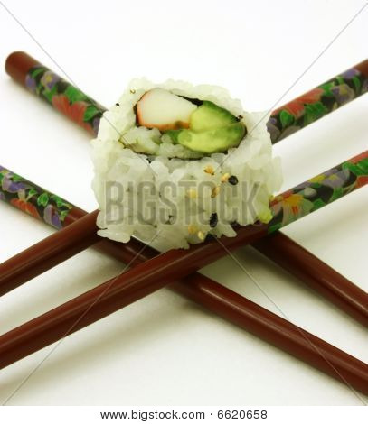 Single sushi on crossed chop sticks