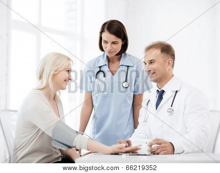 healthcare and medical concept - doctor and nurse with patient measuring blood pressure