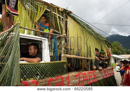 SARAWAK, MALAYSIA: JUNE 1, 2014: Children and musicians of the Bidayuh tribe, an indigenous native tribe of Borneo take part in a street parade celebrating thanksgiving day called the Gawai festival.