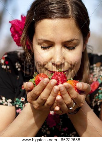 Beautiful Girl Smelling Fresh Strawberries In The Spring