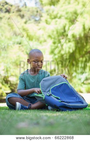 Happy schoolboy opening his schoolbag sitting on grass on a sunny day