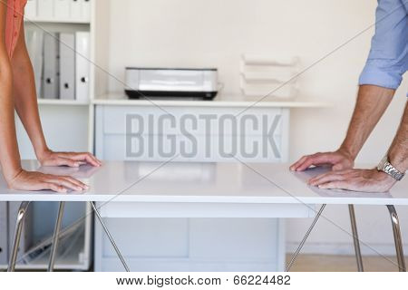 Business partners facing off at desk in the office