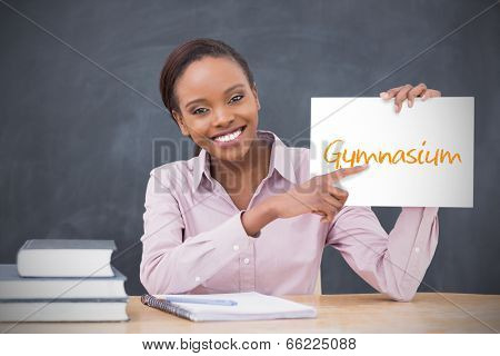 Happy teacher holding page showing gymnasium in her classroom at school