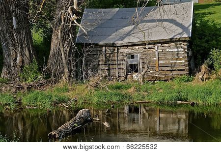 Reflection of an old log cabin in the pond water