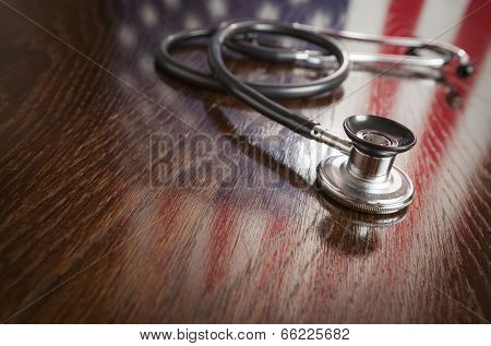 Stethoscope with American Flag Reflection on Wooden Table.