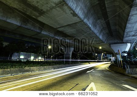 Car light trail under highway