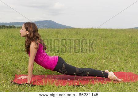Woman Doing Upward Facing Dog In Yoga Outdoors