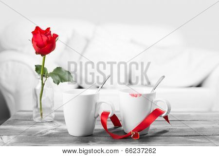 Red lipstick on coffee cups - black and white image with selective red color