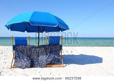 Two Beach Chairs Under A Blue Umbrella On A White Sandy Beach