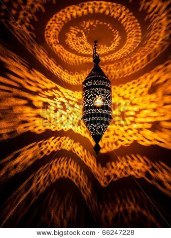 Moroccan lamp with golden swirling light pattern reflecting on wall