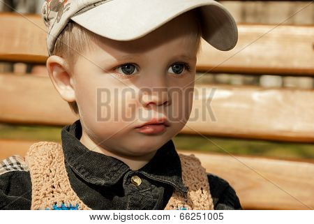 Little Boy In A Cap Outdoors