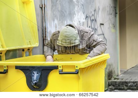 Homeless man near yellow garbage container