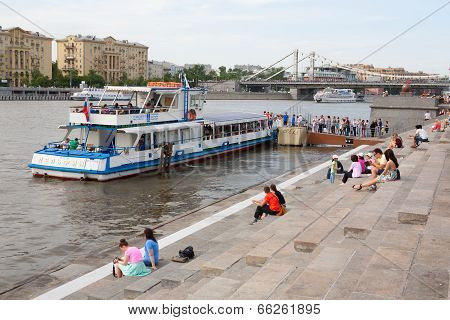 People Resting On The Riverbank. River Ship Is In The Background.
