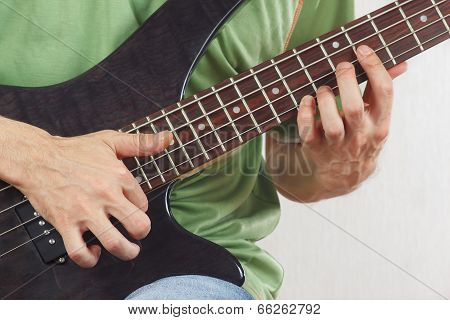 Hands of artist playing the electric bass guitar close up
