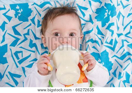 Baby Lying In Crib And Drinking Milk From A Bottle
