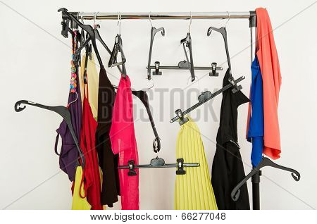 Messy rack of clothes and hangers.