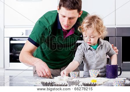 Dad And Son Focused On Baking