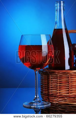 Ripe grapes, wine glass and bottle of wine on colorful background