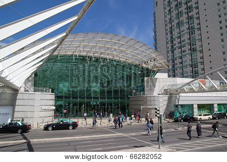 LISBON, PORTUGAL - MAY 26, 2014: People crossing in front of the Vasco da Gama Shopping Mall in Lisbon. The mall is decorated with an ocean theme, with water running over the transparent roof.