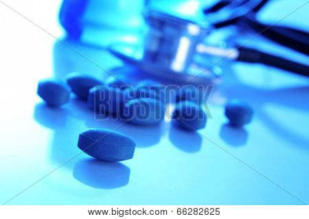 closeup of the desk of a doctors office with pills, a stethoscope and some flasks