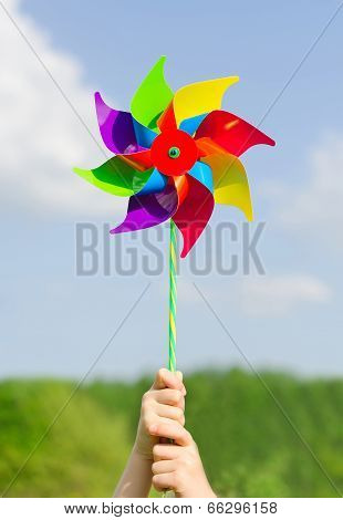 Child Hands Holding Pinwheel Against Blue Sky.
