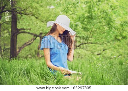 Woman Reads A Book In Summer Park