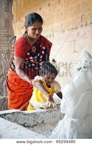 Indian Woman And Child Brings Rice Flour To Ganesha God Statue