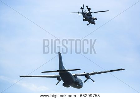 BERLIN, GERMANY - MAY 21, 2014: Transport plane C-160 Transall starts and Tiger combat helicopter go behind the machine in position and secure launch from air, demonstration at ILA Berlin Air Show.