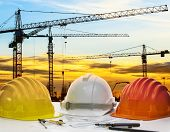 stock photo of land development  - safety helmet and engineering plan with drawing instrument on engineer working table against crane construction and beautiful sun set scene use for construction and land development topic - JPG
