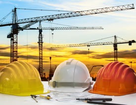 foto of land development  - safety helmet and engineering plan with drawing instrument on engineer working table against crane construction and beautiful sun set scene use for construction and land development topic - JPG