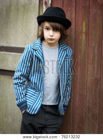 Boy With Hat Leaning Against The Wall