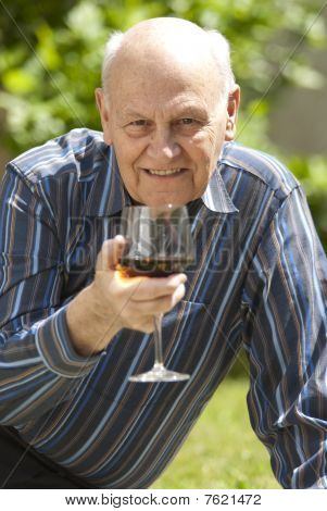 Handsome Senior Man Enjoying A Glass Of Red Wine