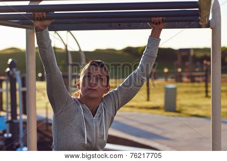 young athletic fitness woman working out at outdoor gym doing pull ups at sunrise