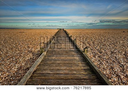 Wharf sea view, wooden footbridge on a rocky beach, blue cloudy sky,H D R