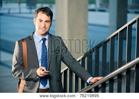 Handsome businessman or manager using phone and going to business appointment or home