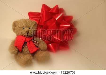 Teddy Bear Sitting Beside A Gift Bow
