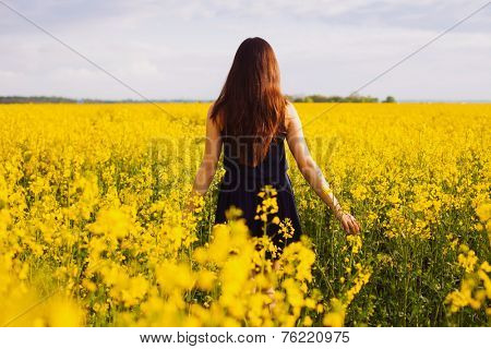 Young woman in sleeveless dress enjoying sunlight and nature on yellow blooming rapeseed field