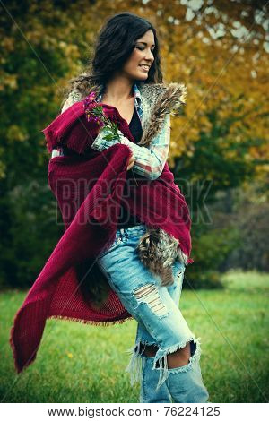 smiling young woman with long curly hair in blue torn jeans, tartan shirt, red wool scarf outdoor shot autumn day in park