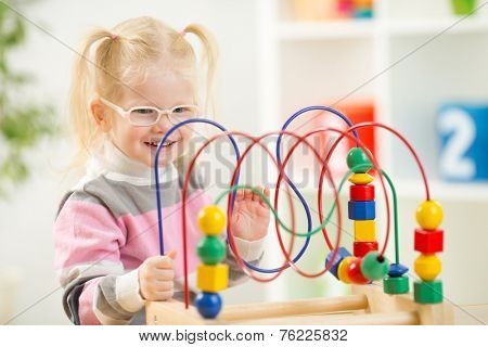 Kid in eyeglases playing colorful toy at home