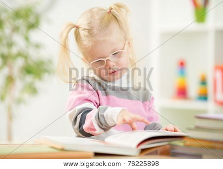 Funny kid in eyeglases reading book