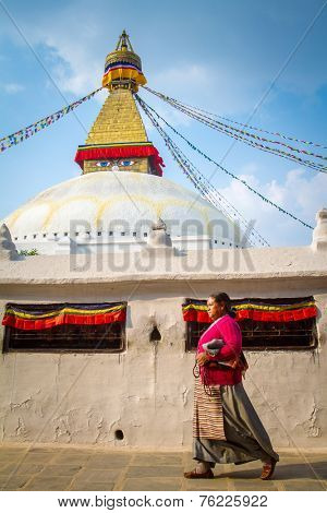KATHMANDU, NEPAL - APRIL 1, 2013: Nepalese woman walking around Boudhanath stupa on April 1, 2013 in Kathmandu. Boudhanath stupa is the center of Buddhism pilgrimage in Nepal.